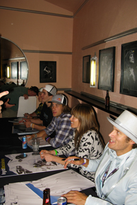 Bobby Brown, Henrik Windstedt, Ingrid Backstrom and Cody Townsend sign posters.