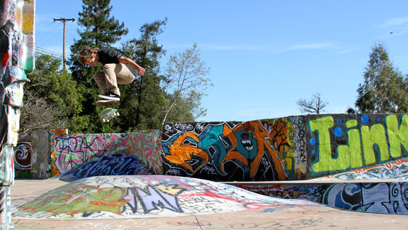 Cory Kennedy flicks a kickflip over a DIY skatepark bump.