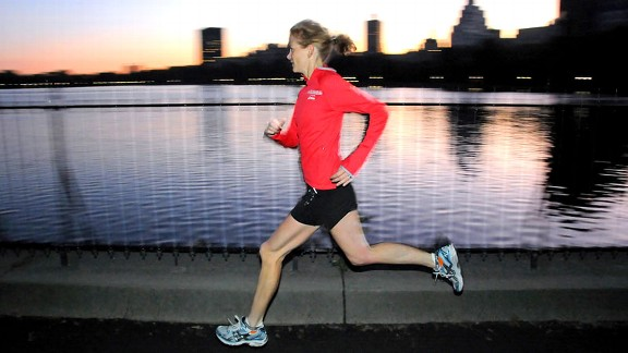 Mary Wittenberg sprints past the Central Park Reservoir at sunshine. She starts most mornings with a run through the park.