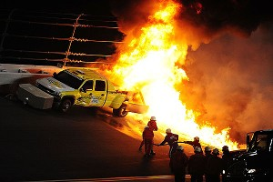 Safety crews work to put out a fire from a jet drier that was hit by driver Juan Pablo Montoya under caution during the Daytona 500 at Daytona International Speedway.