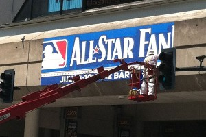 Workers install an All-Star Game sign in downtown Kansas City.