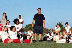 Borislow looms large in women's soccer, posing here in 2011 with members of his daughter's U14 squad and his MagicJack team.