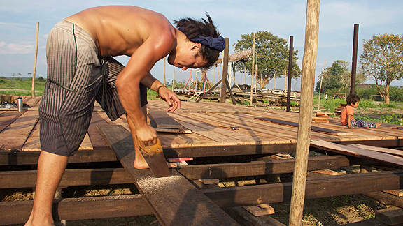 Tamo Campos working to finish the base of the floating garden raft, providing 100 square feet of arable land to the community regardless of flood or high water.