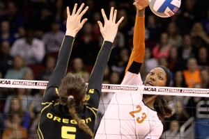 Texas hitter Bailey Webster spikes the ball around the block of Oregon's Canace Finley during Saturday's match.