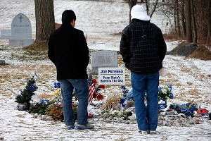 Two Penn State students visit the grave of former Nittany Lions football coach Joe Paterno in State College, Pa., on the first anniversary of his death.