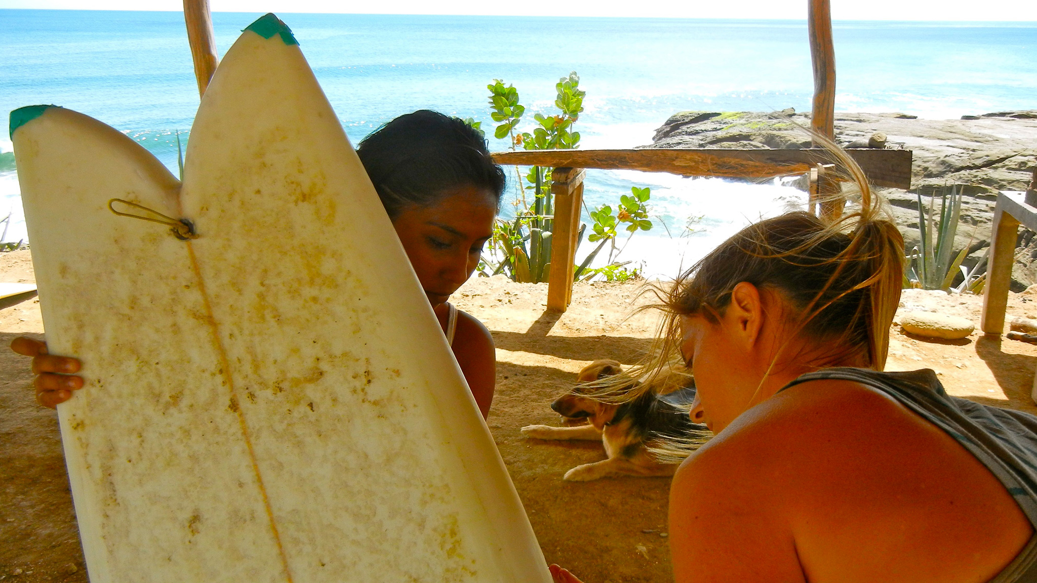 Carly Chivers shows Debora Mora how to repair a board in Nicaragua. Local youth earn credits for use of donated WOO boards and getting travelers in the mix.