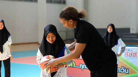 Tamika Catchings provides a passing pointer to a young athlete in Bangkok on Tuesday, as part of the State Department's global efforts to empower women and girls through sports.