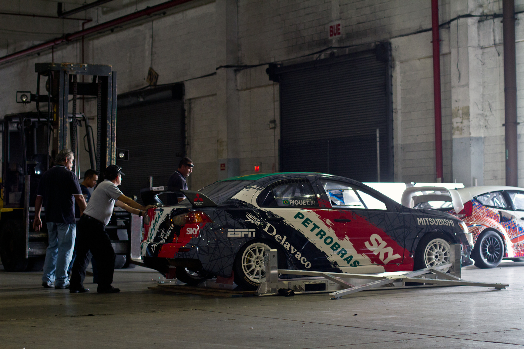 The shipping team makes final preparations to load up rookie RallyCross driver Nelson Piquet Jr.'s Mitsubishi.  It takes strictly manpower to move the cars onto the carrier because all fluids are drained before flying.