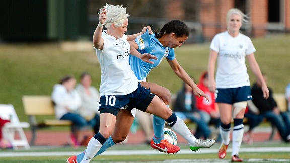 Seattle Reign's Jessica Fishlock holds the jersey of the Chicago Red Stars' Shannon Boxx in the first NWSL game at Illinois Benedictine University on Sunday.