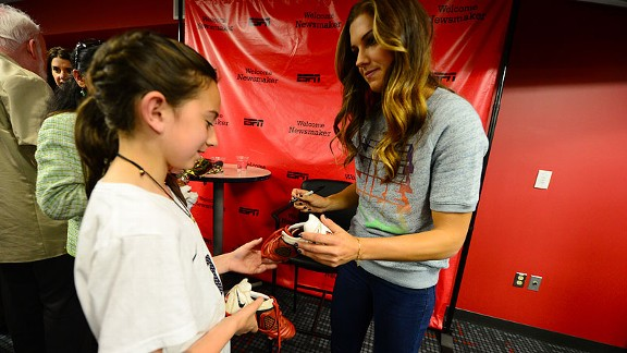 Morgan signs a pair of soccer cleats for a young fan.