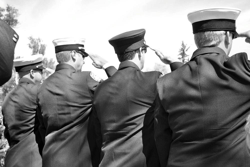 Firefighters salute at  Will Caviness' memorial service