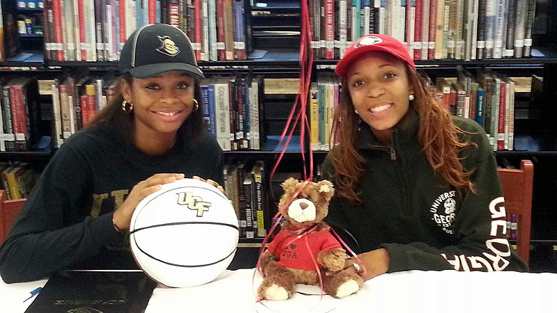Nyala Shuler, left, and Haley Clark of Edgewater (Orlando, Fla.) celebrated the early signing period with a couple pens, some paper, a ball and a bear.  Shuler, a 5-foot-11 guard, signed a national letter of intent to play at Central Florida. Nyala's versatility will help us tremendously on both ends of the floor, UCF coach Joi Williams said. Clark, a 5-9 point guard, signed a national letter of intent with Georgia. She's very creative and has a great point guard mentality, Georgia coach Andy Landers said. I(Photo Courtesy Al Honor)/I