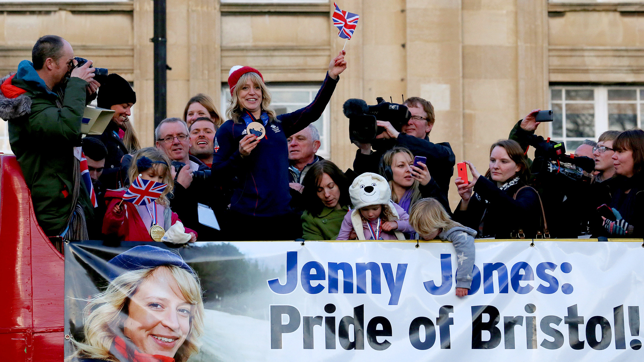 Jenny Jones waves to a crowd of fans from a bus during her post-Sochi hero's-welcome homecoming tour.