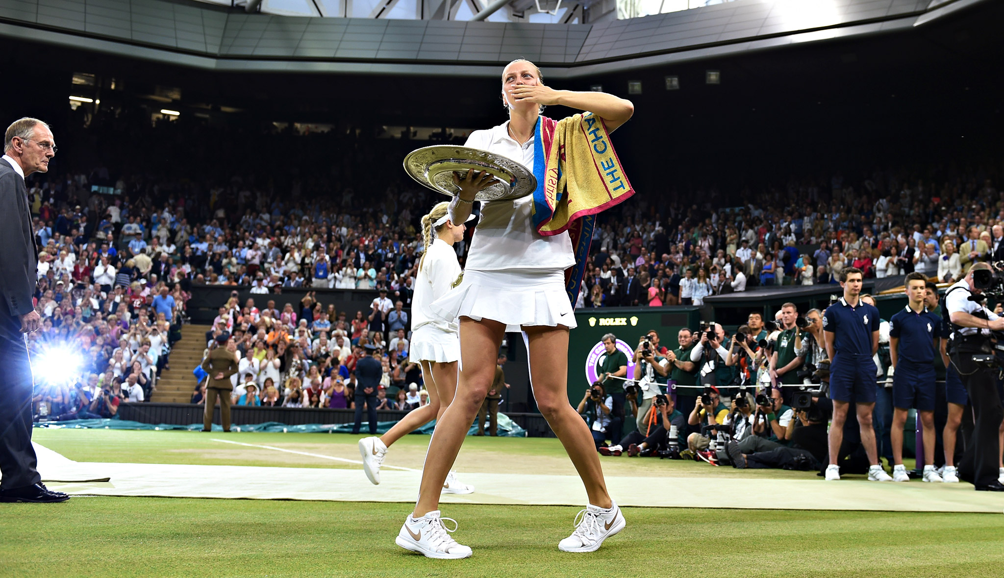 Petra Kvitova blows a kiss to the crowd as she holds the Wimbledon trophy after winning the women's final against Eugenie Bouchard. Kvitova overpowered and overwhelmed Bouchard 6-3, 6-0 in only 55 minutes.