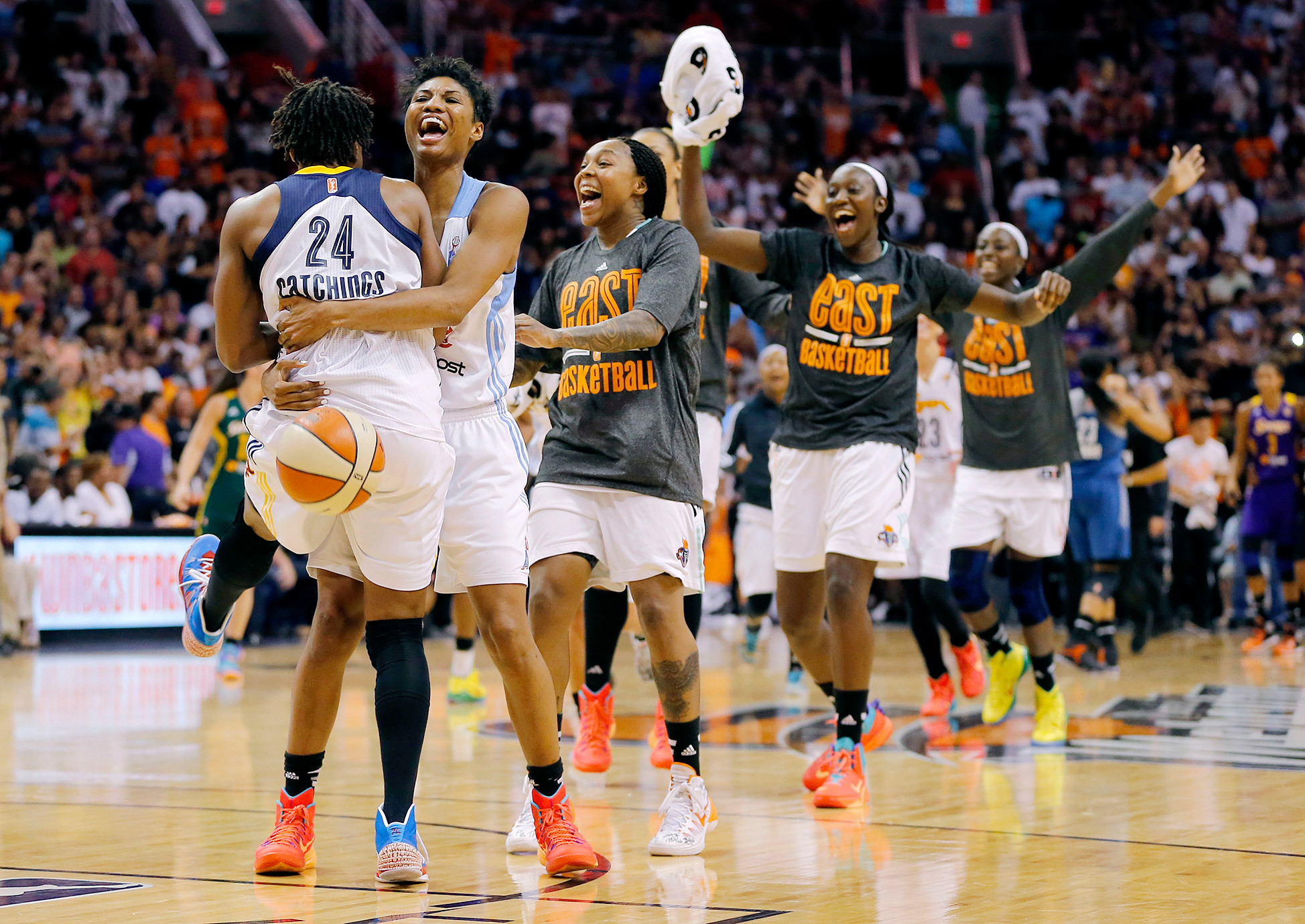 The East's Tamika Catchings of the Indiana Fever is embraced by teammates as time expires in overtime of the WNBA All-Star Game.