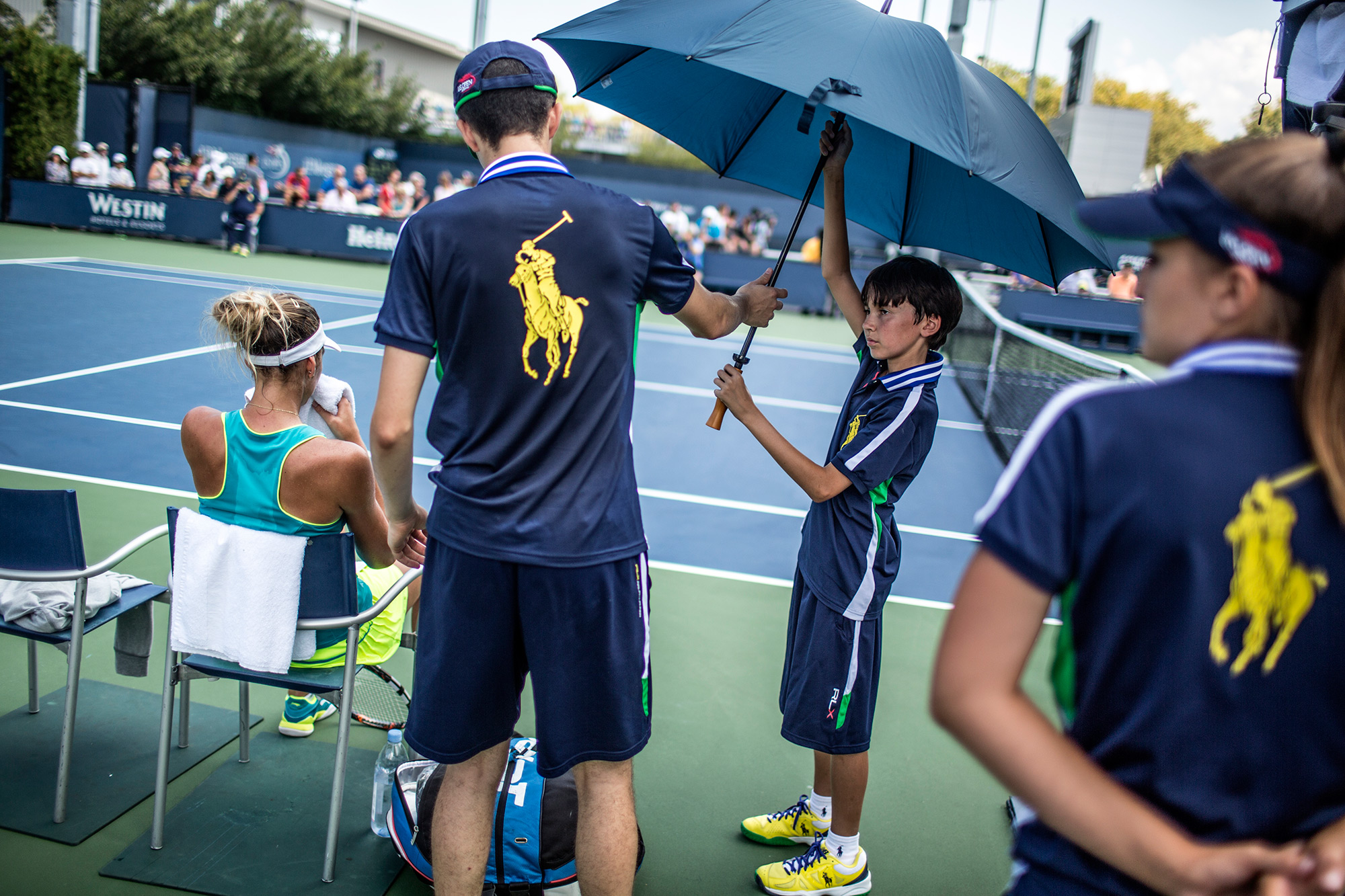 US Open ball persons have a variety of responsibilities -- retrieving stray balls, distributing water and towels and shading the players from the sun. For some of the younger and vertically challenged volunteers, that last task is harder than others.