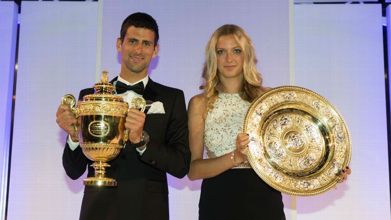 Novak Djokovic poses with the Gentlemen's Singles Trophy and Petra Kvitova with the Venus Rosewater Dish trophy at the Wimbledon Championships 2014 Winners Ball
