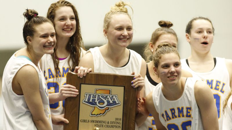 The Carmel (Ind.) High girls swim team hoists the trophy after winning its 30th consecutive state title, a national record.
