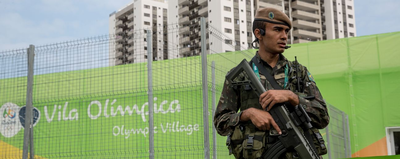 An armed guard stands watch outside the Olympic village.