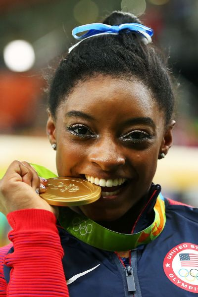 Simone Biles poses with one of her gold medals at the Rio Olympics.