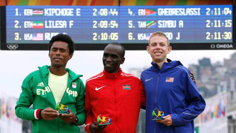 Feyisa Lilesa (silver) of Ethiopia, Eliud Kipchoge (gold) of Kenya and Galen Rupp (bronze) of the United States pose during the traditional flower ceremony after the race.