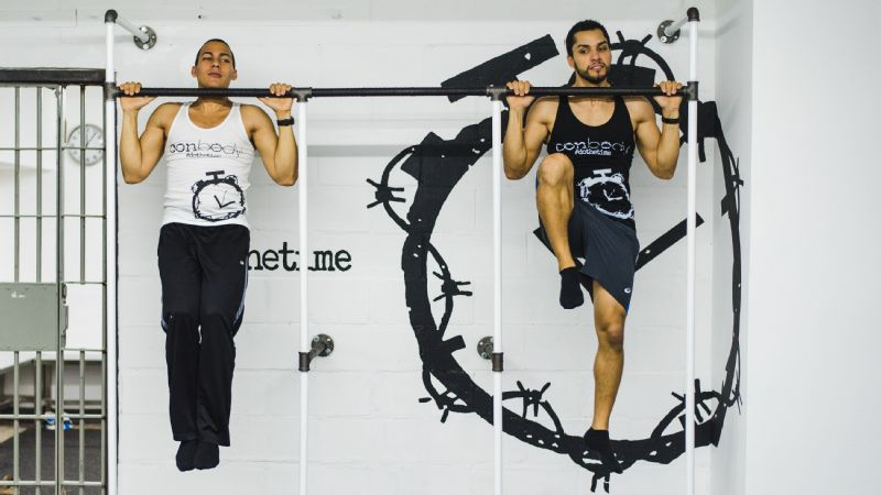 Founder Coss Marte (on left) demonstrating pull-up holds with trainer Shane Ennover.