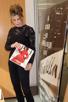 Myers holding the March issue of Elle, which hits newsstands on Tuesday.