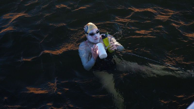 Sarah Thomas, covered in protective sunscreen, taking a nutrition break during the 56-hour Lake Powell swim last fall.