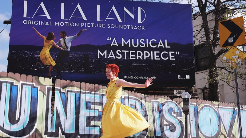 Jillian Meyers does her happy dance in front of a La La Land promotional billboard.