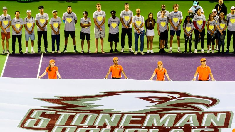 The boys and girls tennis teams from Marjory Stoneman Douglas High School stood on stadium court at the Miami Open on Saturday night.