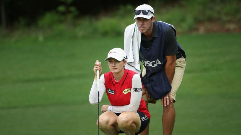 Leader Smith's caddie careful not to push the wrong buttons