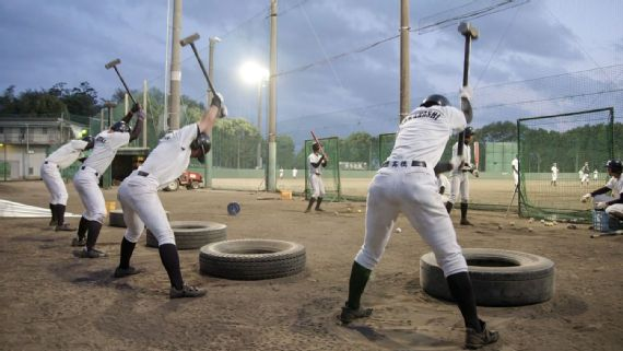 Baseball players exercising with sledgehammers and tires